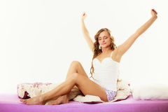 Woman waking up in bed stretching her arms up Royalty Free Stock Photography