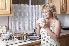 Woman waking up with a coffee. (Dirty dishes) - smiling Stock Images