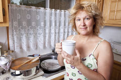 Woman waking up with a coffee. (Dirty dishes Stock Photo