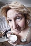 Woman waking up with a coffee. (Dirty dishes fisheye Stock Photo