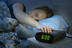 Woman waking up early with alarm clock. Young woman pressing snooze button on early morning digital alarm clock radio Royalty Free Stock Image