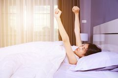 Woman waking up and hand raised on bed in bedroom Stock Images