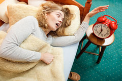 Woman waking up late turning off alarm clock. Stock Photos