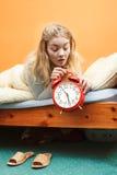 Woman waking up late turning off alarm clock. Stock Photos