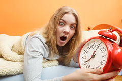 Woman waking up late turning off alarm clock. Stock Photo