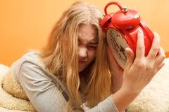 Woman waking up late turning off alarm clock. Royalty Free Stock Image