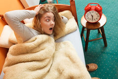 Woman waking up late turning off alarm clock. Royalty Free Stock Images