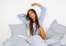 Woman waking up in the morning in bed Stock Photos