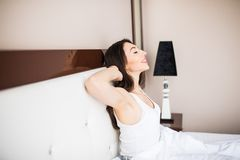 Woman waking up at morning in her bed at home Royalty Free Stock Photos