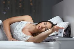 Woman waking up in the night turning off alarm clock stock photography