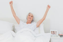 Woman waking up and raising arms in bed Royalty Free Stock Photos