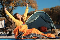 Woman waking up in sleeping bag near tent. Outdoors stock photo