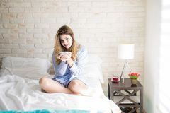 Woman waking up to some coffee. Portrait of a gorgeous young woman sitting on her bed in the morning and drinking some coffee Stock Image
