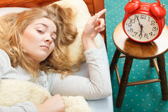 Woman waking up turning off alarm clock in morning Royalty Free Stock Image