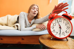 Woman waking up turning off alarm clock in morning Stock Photo