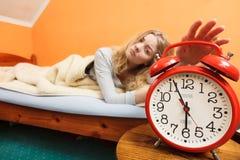Woman waking up turning off alarm clock in morning Stock Photos
