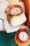 Woman waking up turning off alarm clock in morning Royalty Free Stock Photos