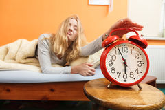 Woman waking up turning off alarm clock in morning Royalty Free Stock Photography