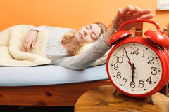 Woman waking up turning off alarm clock in morning. Exhausted woman waking up in bed turning off alarm clock. Young girl in the morning Stock Photography