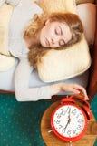 Woman waking up turning off alarm clock in morning Stock Image