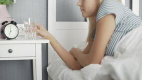 Woman waking up in white bed and drinking water in bedroom
