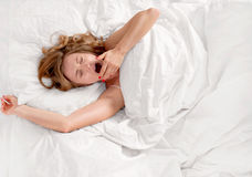 Woman waking up and yawning after sleep on bed Stock Photo