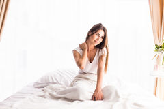 Woman waking up and yawning with a stretch while sitting in bed Stock Images
