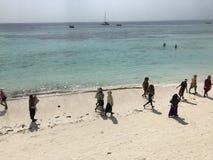 Woman walk along on the beach of Zanzibar, Tanzania - AFRICA. Zanzibar is a Tanzanian archipelago off the coast of East Africa. On its main island, Unguja Royalty Free Stock Photography