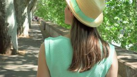 Woman walk along waterfront in slow motion. Behind view of female traveler enjoying vacation outdoor. Young woman in hat walking along waterfront in slow motion stock video footage