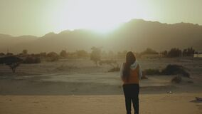 Woman walk in desert and looking Into Horizon. View of desert mountains and blue sea from back of female, slow motion