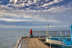 Woman walk with dog on wooden sea pier. Woman sits with dog on wooden sea pier at sunny windy day stock photo