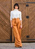 Woman walk in elegant outfit. Fashion and style concept. Woman fashionable brunette stand outdoors wooden background. Girl with makeup posing in fashionable royalty free stock image