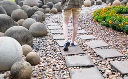 Woman walk in the garden. Woman walk on the brick in garden, attend to shot her leg Stock Image
