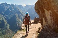 Woman walk on narrow mountain path Stock Photos