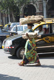 Woman walk on the street. Mumbai, india. Woman walking on the streets of Mumbai. Women carrying objects on the head. Traffic on the streets of the city royalty free stock photos