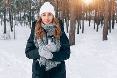 Woman on a walk in the winter forest drinking tea from a thermos Stock Photography