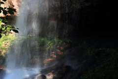 A woman walked with an umbrella walking in the cave behind the waterfall cave. Sunlight falls on, by the light refraction, the beautiful rainbow Royalty Free Stock Images