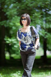 Woman walking. Young adult woman with hands in pockets walking it the park Stock Photography