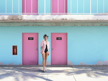 Woman walking from abandoned motel with pink doors. vacation concept Royalty Free Stock Images