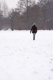 Woman walking across snow covered field Royalty Free Stock Image