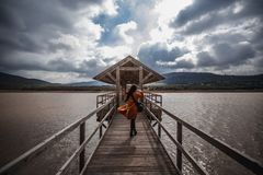 Woman walking across wooden bridge across lake on cloudy day long exposure royalty free stock photography