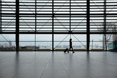 Woman walking in airport terminal Stock Photos