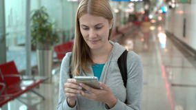 Woman walking in airport terminal. Using smartphone, browsing, messaging with friends, reading news. Beautiful positive young woman walking in airport terminal stock video footage