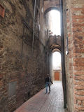 Woman walking through alleyway in Sienna Italy Royalty Free Stock Photos