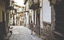 Woman Walking Alone Along a Narrow Street Stock Photos