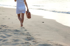 Woman walking alone on the beach Royalty Free Stock Photography