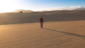 Woman walking alone in the desert. Woman walking alone in the desolate desert at sunset Royalty Free Stock Images