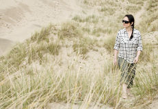 Woman walking alone in sand dunes Stock Photo