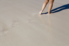 Woman walking along a beach Stock Images
