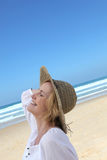 Woman walking along beach Stock Image